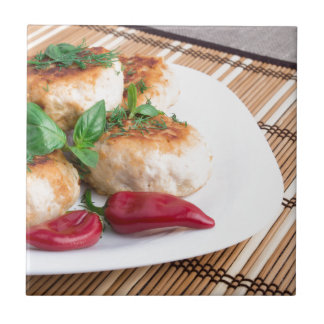 Closeup view of the fried meatballs on a stripe small square tile