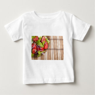 Closeup view on a fragment of a plate with salad baby T-Shirt