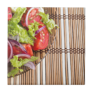 Closeup view on a fragment of a plate with salad small square tile