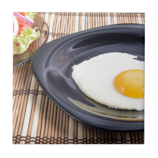 Closeup view on fried eggs with yolk on a plate small square tile