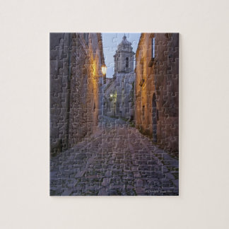 Cobbled alleyway of old city lit up at night jigsaw puzzle