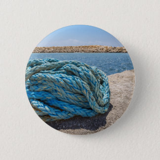 Coiled blue mooring rope at water in greek cave 6 cm round badge