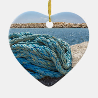 Coiled blue mooring rope at water in greek cave ceramic heart decoration
