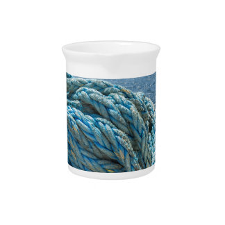 Coiled blue mooring rope at water in greek cave drink pitcher