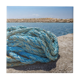 Coiled blue mooring rope at water in greek cave small square tile