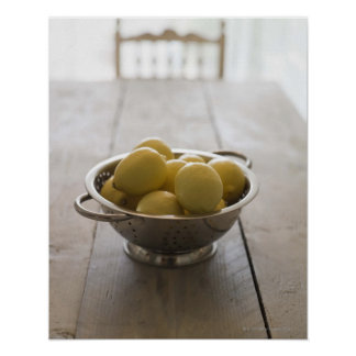 Colander with lemons on wooden table poster