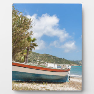 Colorful boat lying on greek beach display plaques