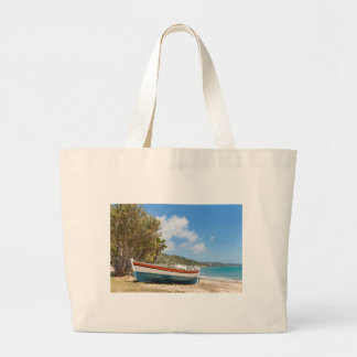Colorful boat lying on greek beach large tote bag