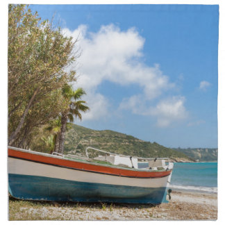 Colorful boat lying on greek beach napkins