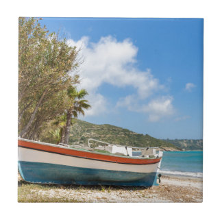 Colorful boat lying on greek beach small square tile
