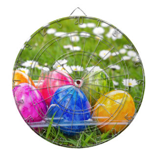 Colorful painted easter eggs in grass with daisies dartboard with darts