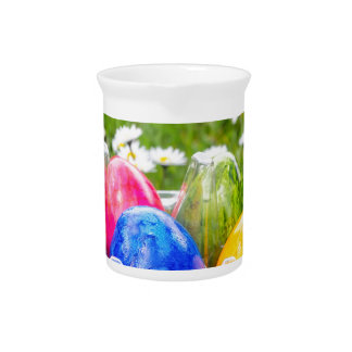 Colorful painted easter eggs in grass with daisies pitcher
