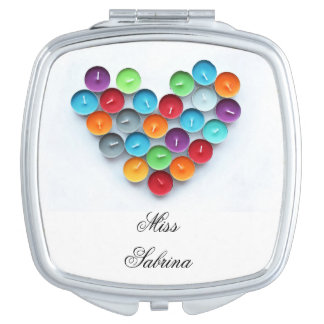 Colorful scented candles arranged as love heart travel mirrors