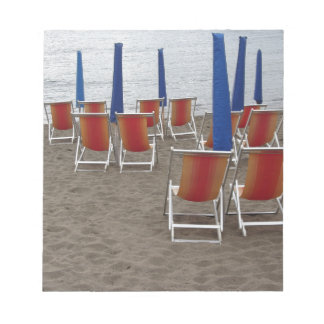 Colorful wooden chairs at sand beach notepad