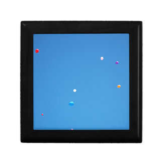 Colourful balloons released into a blue sky. gift box