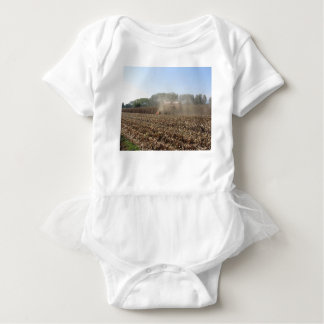 Combine harvesting corn crop in cultivated field baby bodysuit