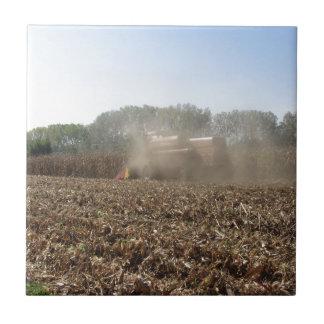 Combine harvesting corn crop in cultivated field ceramic tile