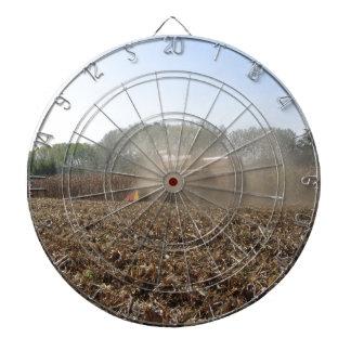 Combine harvesting corn crop in cultivated field dartboard