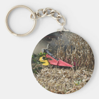 Combine harvesting corn crop in cultivated field key ring