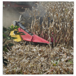 Combine harvesting corn crop in cultivated field napkin
