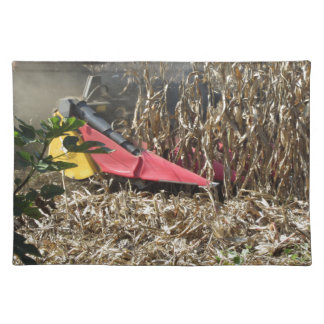 Combine harvesting corn crop in cultivated field placemat