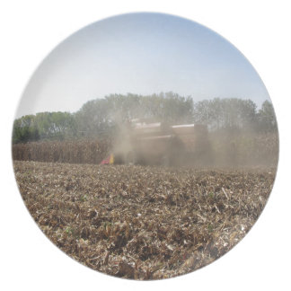 Combine harvesting corn crop in cultivated field plate