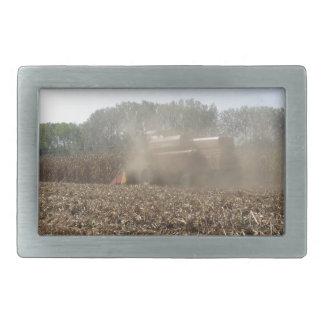 Combine harvesting corn crop in cultivated field rectangular belt buckle