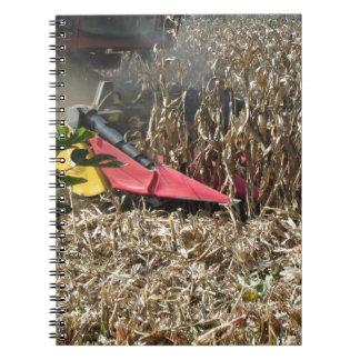 Combine harvesting corn crop in cultivated field spiral notebook