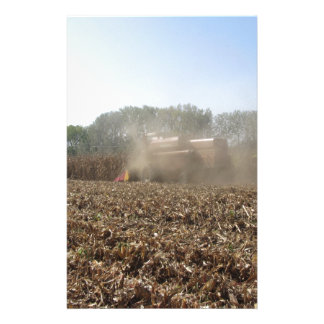 Combine harvesting corn crop in cultivated field stationery