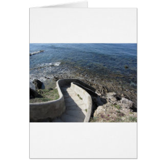 Concrete staircase down to the sea . Spiral stairs Card