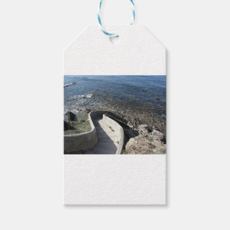 Concrete staircase down to the sea . Spiral stairs Gift Tags