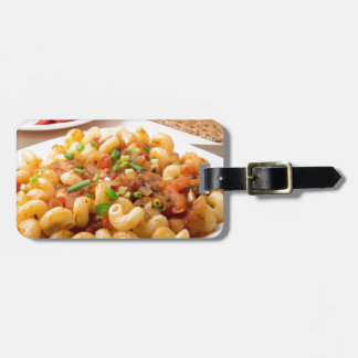 Cooked pasta cavatappi with stewed vegetable sauce luggage tag