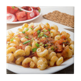 Cooked pasta cavatappi with stewed vegetable sauce tile