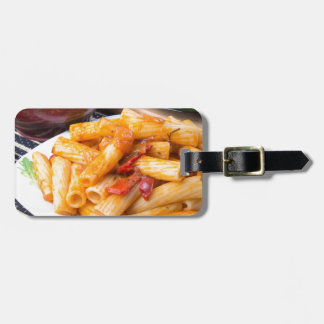 Cooked rigatoni pasta, seasoned with pepper luggage tag