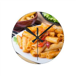 Cooked rigatoni pasta, seasoned with pepper round clock