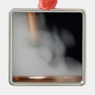 copper pipe of a distillery with steam. Silver-Colored square decoration