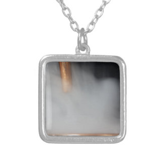 copper pipe of a distillery with steam. silver plated necklace