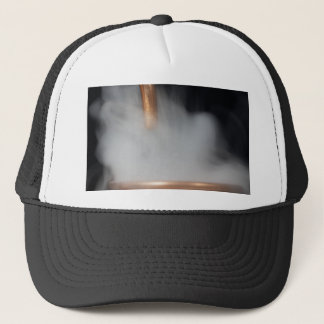 copper pipe of a distillery with steam. trucker hat