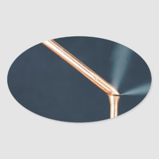 Copper pipes with a leak and steam. oval sticker