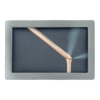 Copper pipes with a leak and steam. rectangular belt buckle