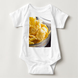 Cornflakes in a transparent bowl closeup baby bodysuit