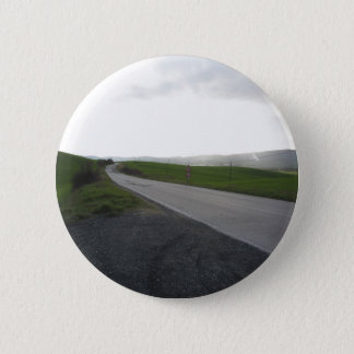 Country road over rolling green hills and valleys 6 cm round badge