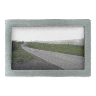 Country road over rolling green hills and valleys belt buckles