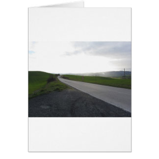 Country road over rolling green hills and valleys card