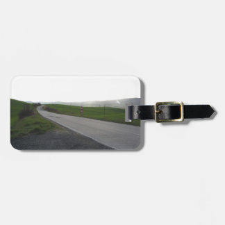 Country road over rolling green hills and valleys luggage tag