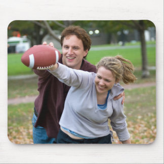 Couple playing football in park mouse pad