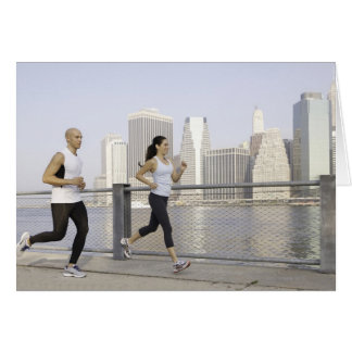Couple running on pier with city in background card