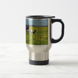 Cow with calves grazing in meadow with dandelions travel mug