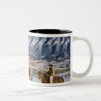 Cowboy and Cowgirl riding Horse through the Snow Coffee Mug