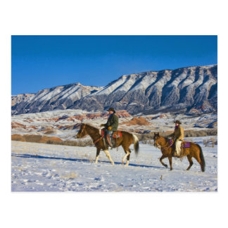 Cowboy and Cowgirl riding Horse through the Snow Postcard